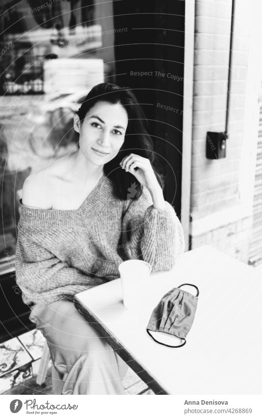 Young lady is drinking coffee at the cafe cup woman portrait young face mask lockdown lifted beautiful female casual brunette table person adult attractive