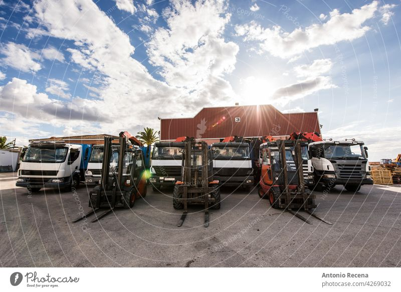 Trucks and forklifts lined up in construction company with industrial warehouse behind. Wide angle image on cloudy day. truck wide angle vehicle transportation