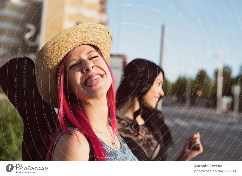 pink haired woman in hat sticking out tongue at camera young attractive 20s joy people person youth urban women pretty pretty people outdoors city walking