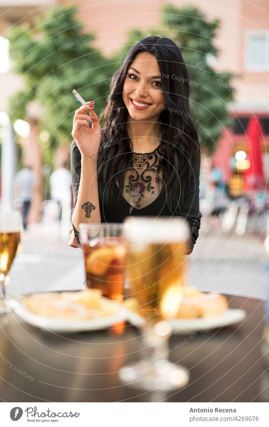 gorgeous Spanish woman smokes cigar and drinks beer on the terrace of a bar young attractive 20s joy people person youth urban women pretty pretty people
