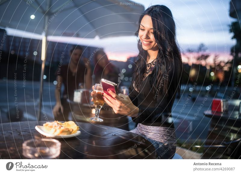 woman looking smartphone in bar terrace while drinking beer young attractive 20s joy people person youth urban women pretty pretty people outdoors city sit