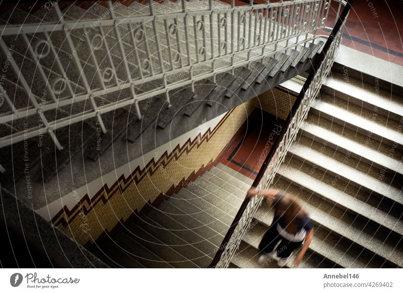 Young woman running down the antique staircase top view, royal vintage luxury style building and architecture background mystery fashion abstract retro playful