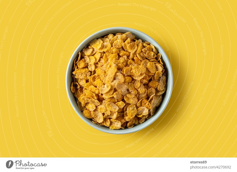 Corn flakes in a blue bowl american breakfast brunch cereal corn crispy crunchy dairy diet dry eat energy food healthy snack table yellow