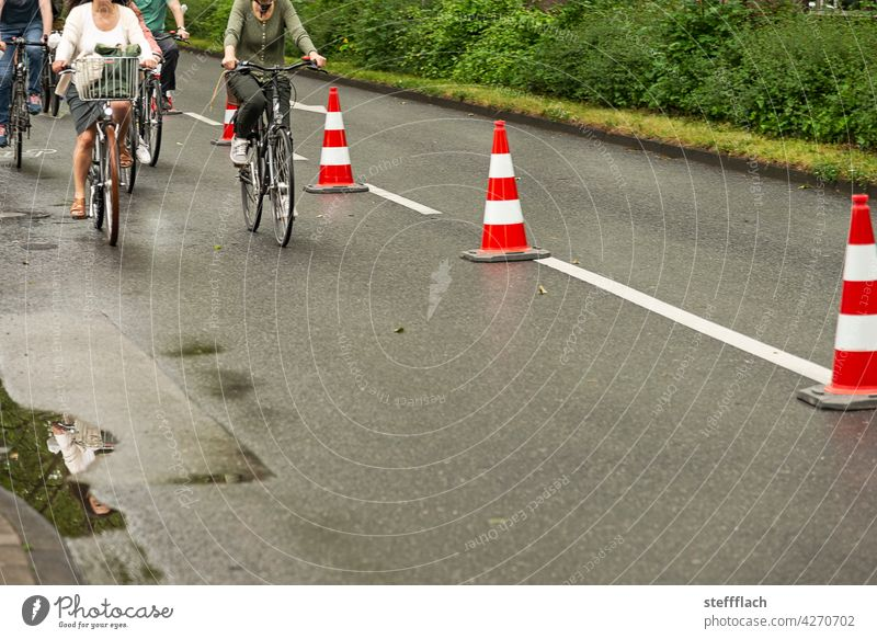 Bicyclists on a half of the road closed off with traffic cones Bicycle Cycling Cycle path, traffic, road, environment, city, urban bicycles persons turnaround