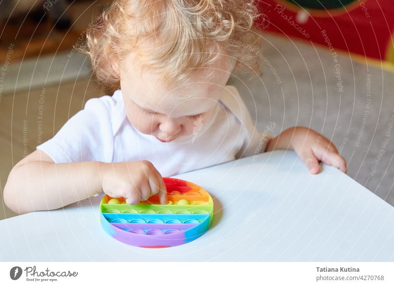 Popular Anti stress toy Pop It. Child Playing With The Pop It Fidget Toy. Happy childhood, popular educational games. popit anti stress antistress sensory