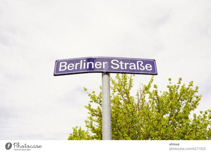 """bent street name sign """" Berliner Straße """" in front of a green bush and cloudy sky Street sign street sign Orientation berlin street Bend corrupted dwell Central"""