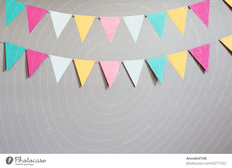 Colorful party flags over cement concrete gray wall texture background, pastel birthday colored flags with copy space Holiday concept happy music baby wedding