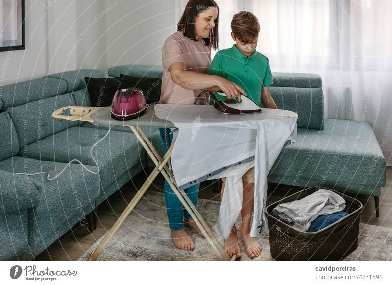Mother teaching her teen son to iron mother ironing home helping ironing board laundry basket clothes together living room housewife teenager kid woman child