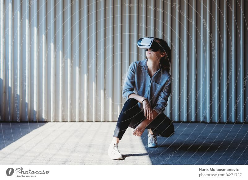 young woman with vr goggles outdoors posing, virtual reality experience 3d adult background casual caucasian city creativity cyber device digital entertainment