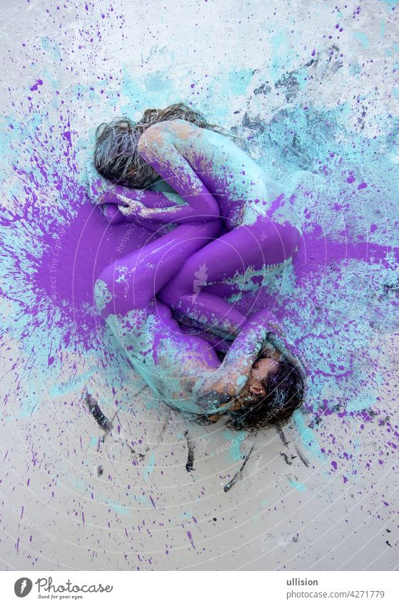 Two artistically abstract painted young sexy women, girlfriends in pink, purple, turquoise and white color lying like a Yin Yang symbol on the floor in the studio, copy space.