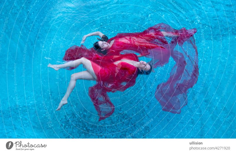 Top view of a beautiful young sexy dark-haired women relaxed in red dress floating weightlessly elegant in the water of the pool, copy space two swimmer girl