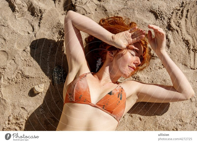 Overhead shot of a sexy redhair bikini woman redhead laying in the sunshine on the sand on the beach portrait skin outside pale seductive summertime outdoors