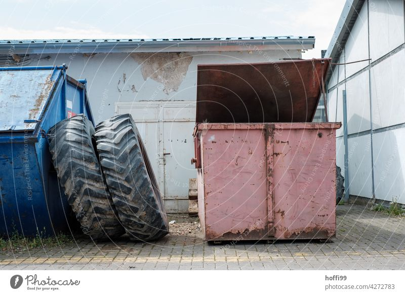 Still life of two scrap metal containers with large tractor tires on a workshop yard tractor tyre Container Workshop yard waste Recycling container recycle