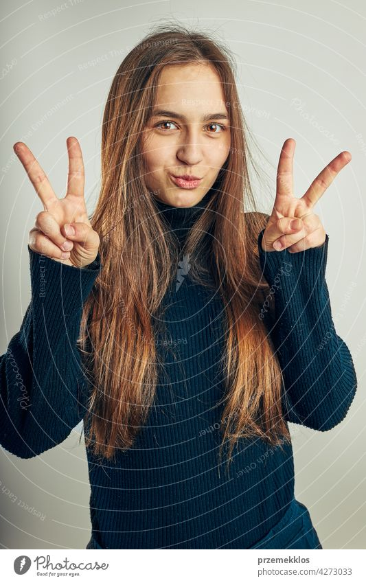 Excited girl gesturing peace sign. Portrait in positive mood. Girl making victory sign gesture portrait headshot woman model person female young teenager pretty