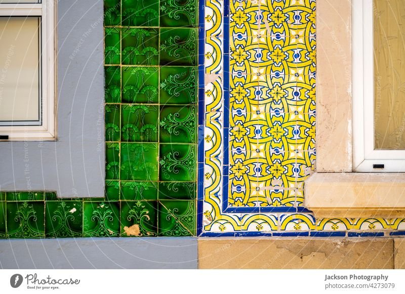 Close up of typical tiles on the facade of old houses in Olhao, Portugal portugal olhao azulejo detail close up architecture azulejos in a row afternoon algarve