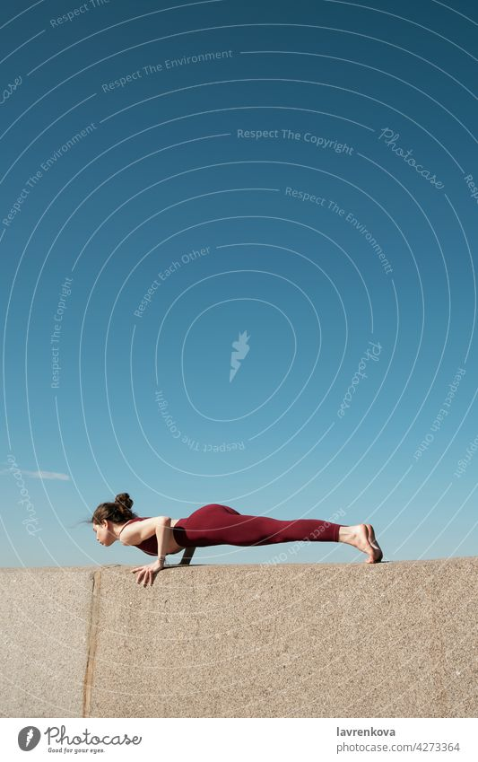 Young brunette woman practicing chaturanga dandasana on top of concrete wall on a beach in front of blue sky yoga yogini plank pose sport athletic female