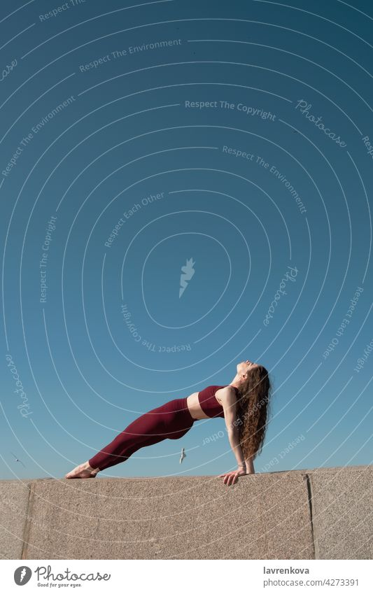 Young brunette woman practicing Purvottanasana pose on top of concrete wall on a beach in front of blue sky Reverse Plank Pose yoga yogini sport athletic female