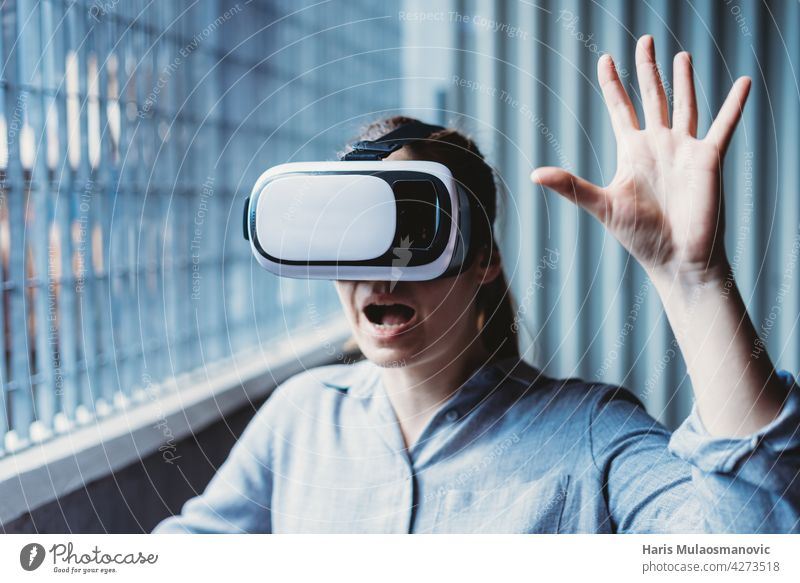 woman with vr goggles and facial expression enjoying virtual reality experience 3d adult background casual caucasian city creativity cyber device digital