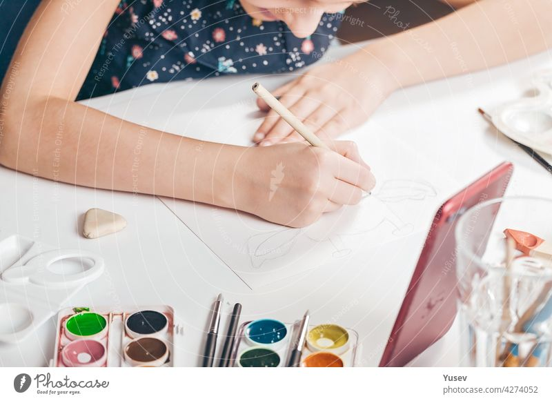 The hands of a cute caucasian girl are drawing a pencil sketch. A girl is watching an online lesson on a smartphone. Classes with children at home. Hands in the frame