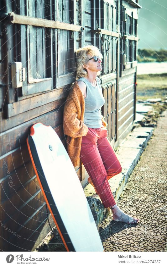 Portrait of a young mature blonde caucasian woman outdoor in a wooden house close to a beach area with a bodyboard and sunglasses.  Lifestyle concept. lifestyle