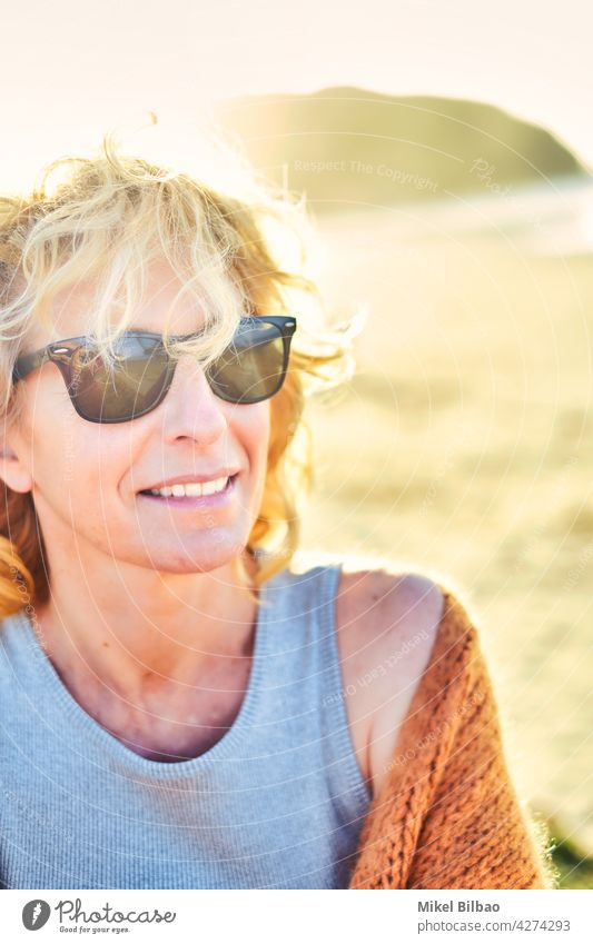 Portrait of a young mature blonde caucasian woman with sunglasses outdoor in a beach in a sunny day.  Lifestyle concept. lifestyle women relaxing travels