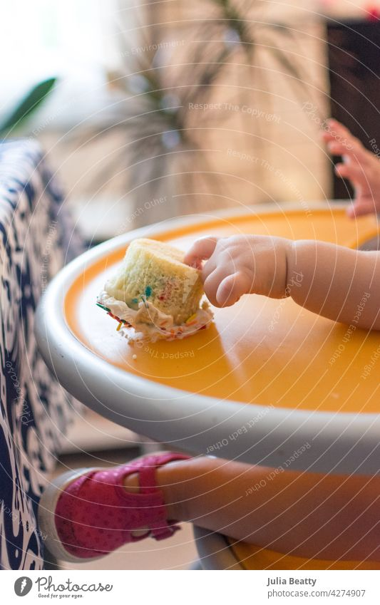 First birthday/first cake: one year old baby reaching out to overturned cupcake on high chair first birthday smash baby led weaning self feed 100 foods dessert