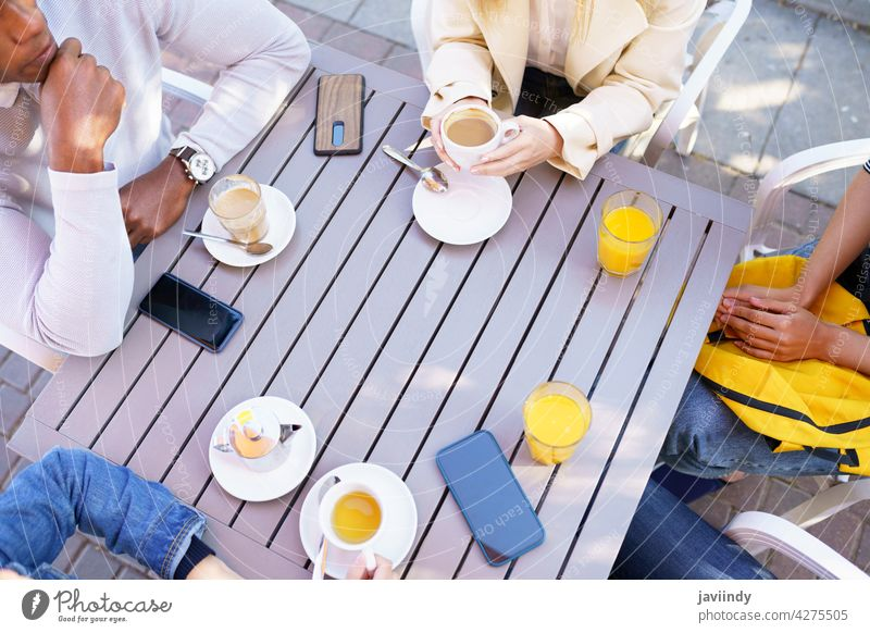 Top view of people drinking some beverages sitting at the table on the terrace of a bar. coffee cafe cup friends tea unrecognizable meeting smartphone lifestyle