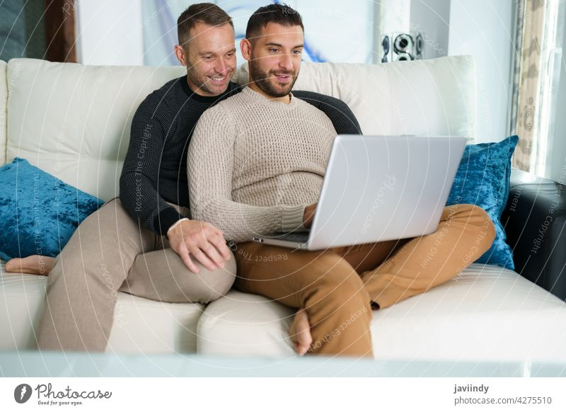 Gay couple consulting their travel plans together with a laptop. gay men homosexual lgbt lgbtq male relationship boyfriend people 30s togetherness man lifestyle