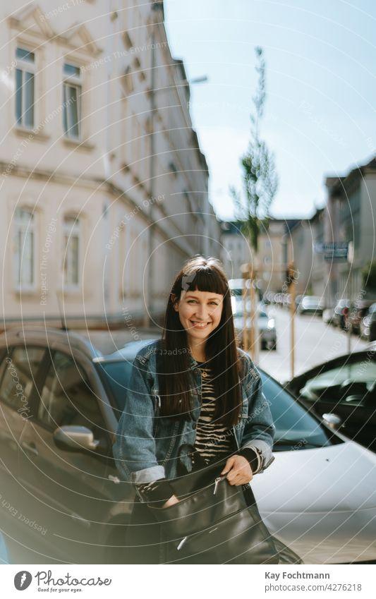 young woman smiling at camera adult attractive beautiful carefree cars casual caucasian cheerful chic cute denim elegant eyewear female femininity girl glasses