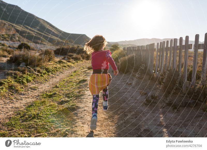 Little girl running through the Spanish landscape, Rambla del Playazo, Cabo de Gata - Nijar Natural Park, Spain national park Andalusia Iberian