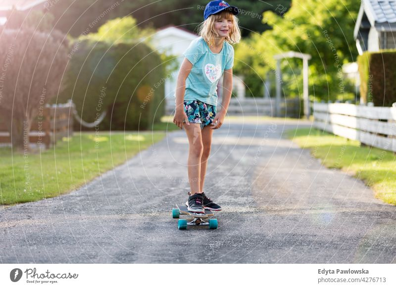 Little girl skateboarding in campsite, Texel, Holland sea camping family people girls children kids Dutch Europe Netherlands Outdoor summer day park active fun