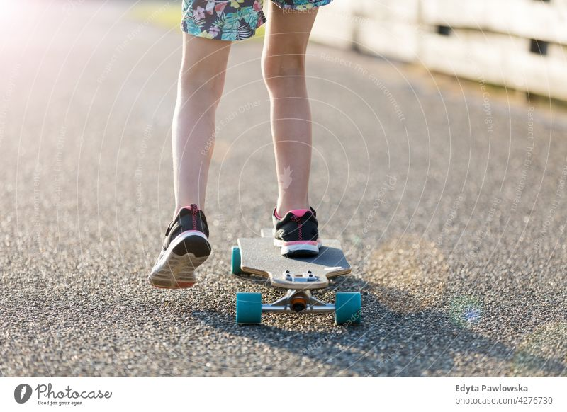 Little girl skateboarding in campsite Texel sea camping family people girls children kids Dutch Europe Holland Netherlands Outdoor summer day park active fun