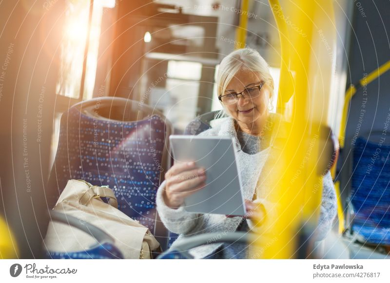 Senior woman using tablet, while riding public bus senior seniors pensioner pensioners casual outdoors one person retiree retired outside retirement aged old