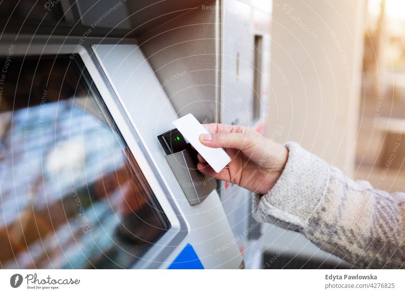 Woman purchasing fare for public transit holding technology using wireless senior seniors pensioner pensioners woman casual outdoors one person retiree retired