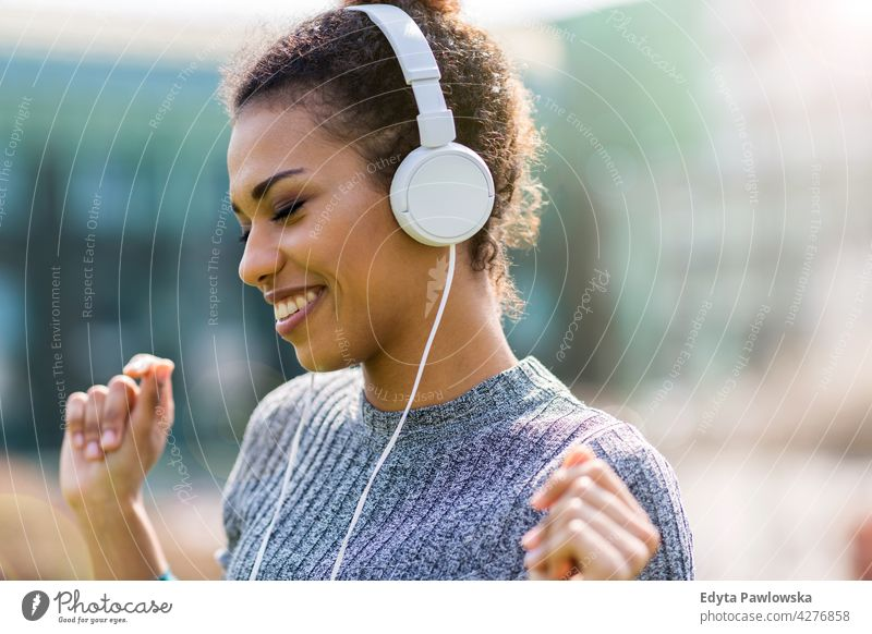 Happy young woman listening music in headphones in the city outdoors day positivity confident carefree people young adult casual beautiful attractive female