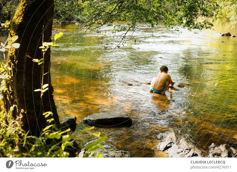 Young boy sitting and playing in the river back view young boy sitting River lifestyle male person kid people cute portrait education Playing learning nature
