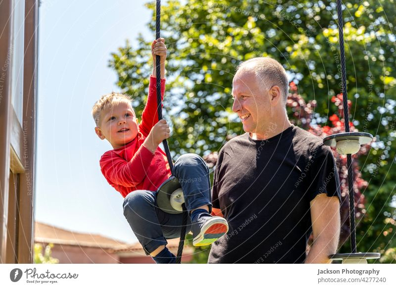 Father playing with his 3 years old son on the playground fun father kid toddler children kids portrait nature laughing bonding togetherness parenthood
