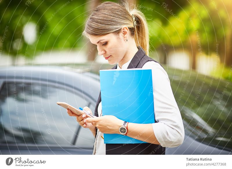 A young business woman with a folder for papers in her hands looks at her smartphone businesswoman texting manager person busy professional office female
