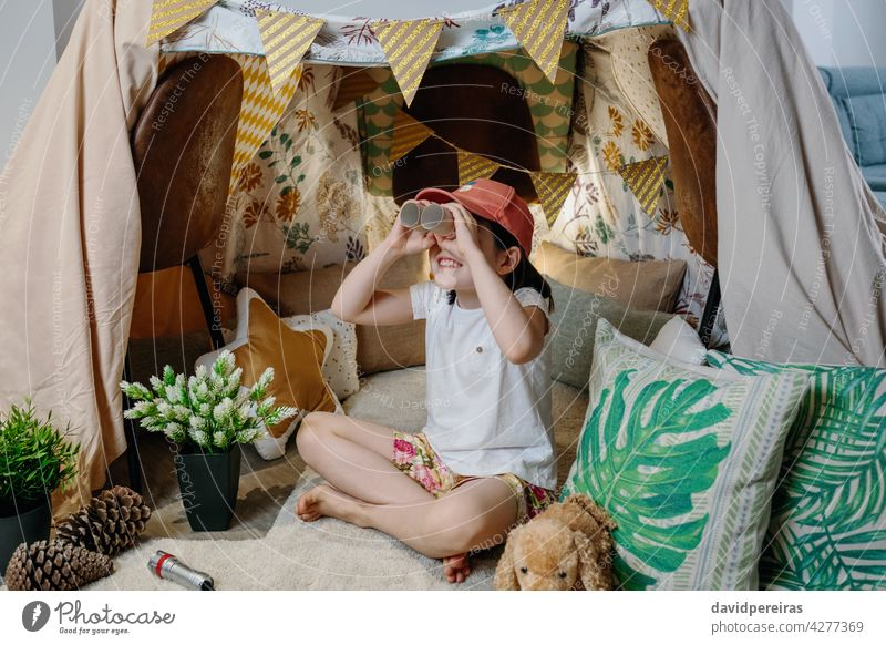 Girl playing with cardboard binoculars while camping at home happy girl observing vacation diy tent smiling carton toilet paper tubes holding toys female little