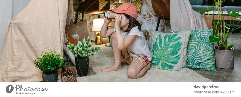 Girl playing with cardboard binoculars while camping at home girl observing diy tent staycation toilet paper tubes carton banner web header panorama panoramic