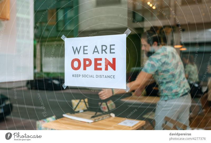 Commercial reopening poster after coronavirus sign cartel we are open keep social distance workers placing tables chairs covid-19 preparing message man