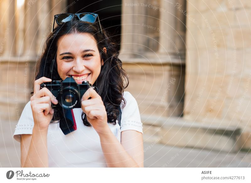 Happy tourist woman taking pictures of the old town with a retro camera young happy smile toothy photo photography summer girl people lifestyle travel monument
