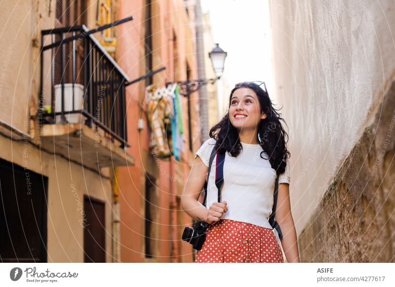 Young happy tourist woman walking down an european city alley with a camera travel vacation girl holiday lane backstreet backpack old town summer spring one