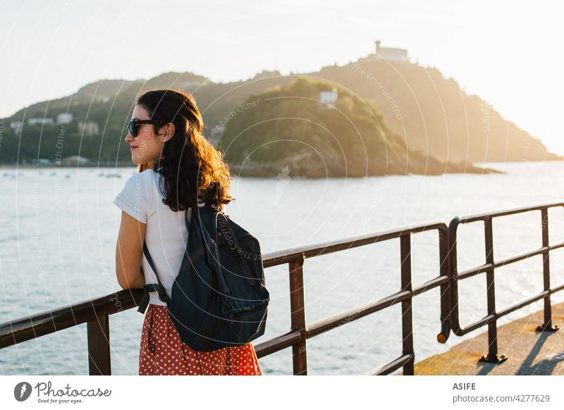 Young tourist woman enjoying the view of San Sebastian bay in Spain at sunset young happy Donostia sea beach La Concha beach island Santa Clara Basque country
