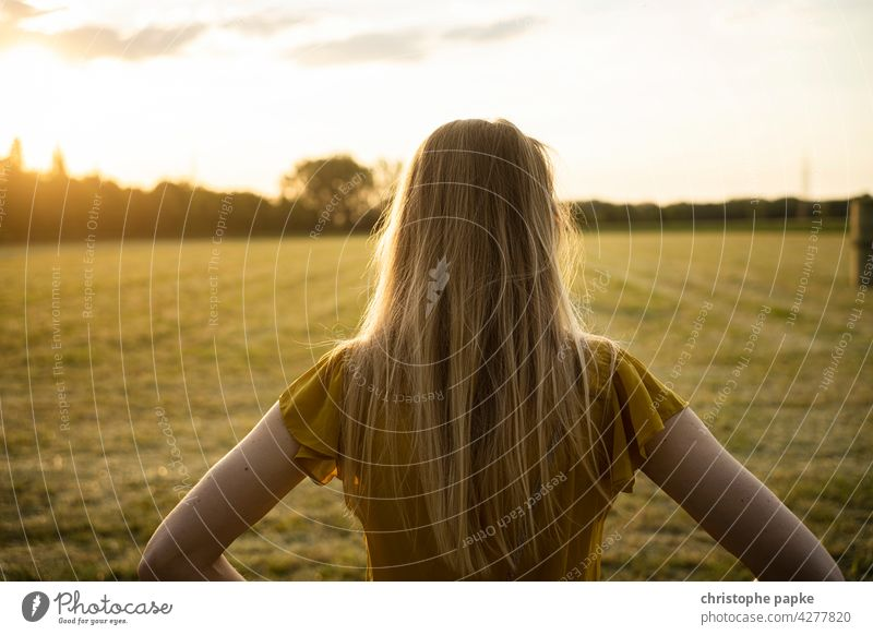 Woman looking at field in evening light Blonde To go for a walk Field Evening Evening sun Agriculture plants Grain Agricultural crop Plant Growth Summer
