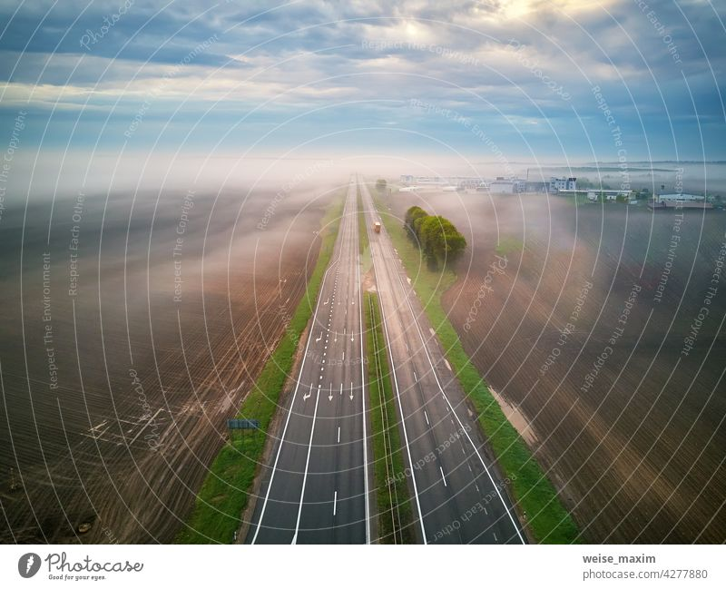 Aerial view of a highway covered by fog. Early misty morning. Road in rainy spring summer fields. road cloud weather overcast transport rural sky scene roadway