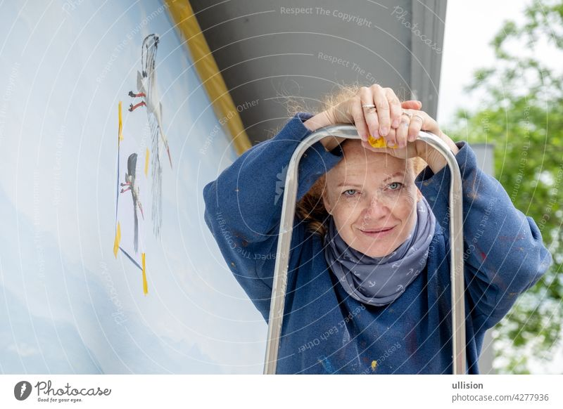 Woman, painter, artist in her forties or fifties with freckles and red hair stands on a ladder with a small brush in her hand, copy space 40s 50s mural painting