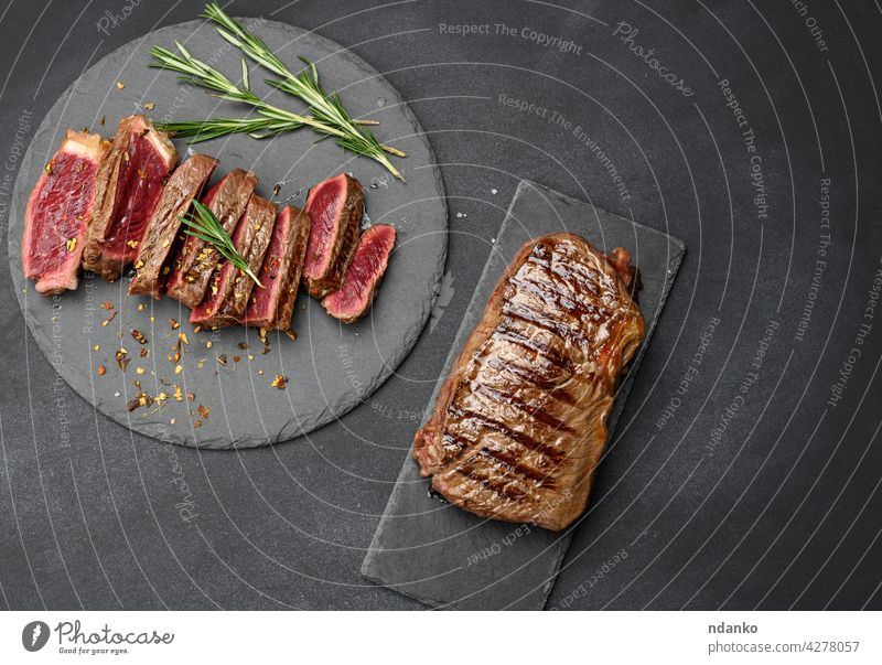 fried beef steaks cut into pieces on a black board, the degree of doneness rare with blood above banner barbecue bbq beefsteak bloody cooked dinner fat fillet