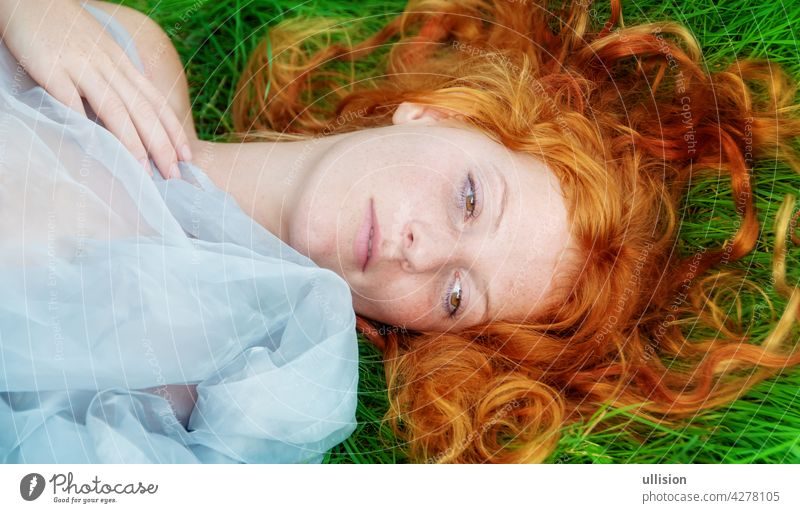 Portrait of a beautiful young sexy red-haired woman, lying in the spring sun in happiness, relaxing on the grass, the red hair draped freely around the head.