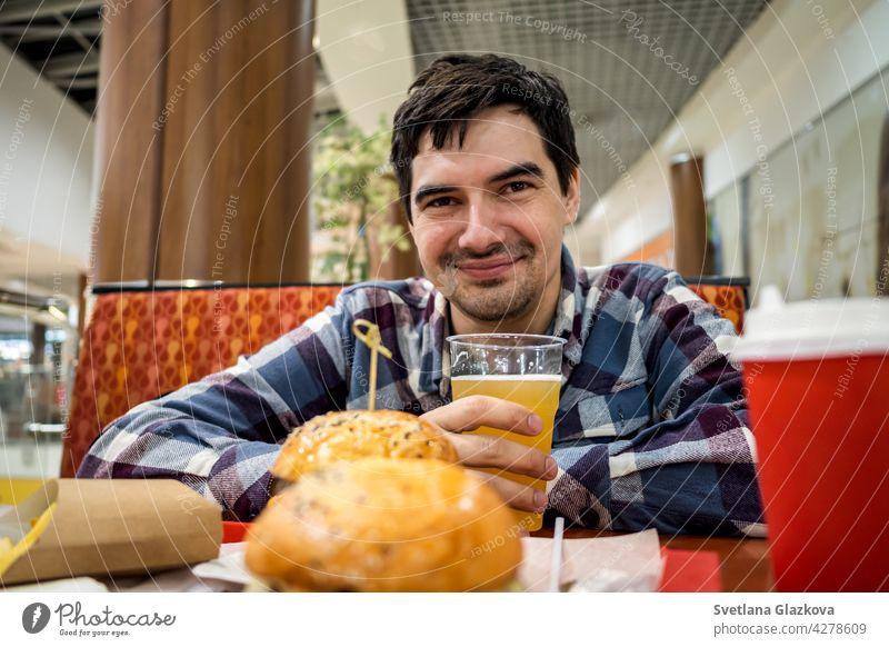 man eating fast food burger and drinking beer alone in the open area of a restaurant in a shopping mall meal bar happy pub male people lunch dinner hamburger